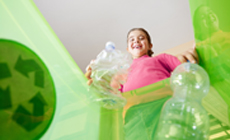 photo of girl throwing bottle in recycle bin